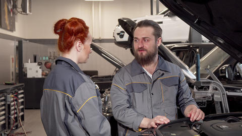 Bearded mechanic talking to his female coleague at the automobile workshop Footage