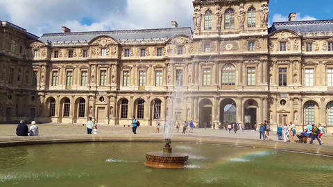 View of famous Louvre Museum with fountains in courtyard of Louvre Palace in a sunny morning, Paris, Live Action