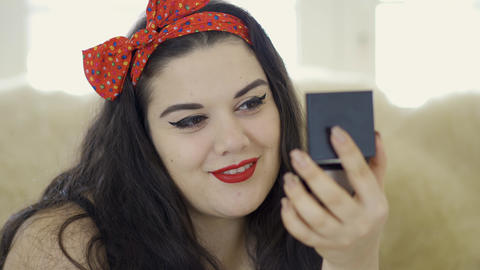 Portrait of attractive young plus size girl doing make-up looking in the mirror Footage