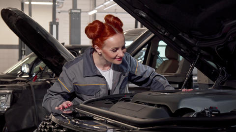 Attractive female car mechanic examining automobile with an open hood Footage