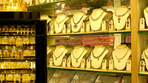 set of gold necklaces, chains and gold bracelets in a showcase of a jewelry store. Beautiful gold Live Action