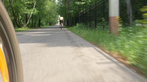 modern bicycle wheel spins riding along bushy green park Footage