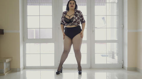 Pretty plus size girl posing for the camera, dancing, shaking her hair. A Footage