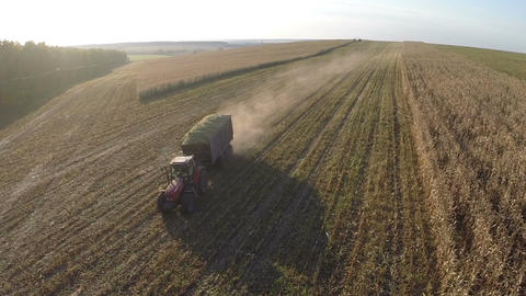 Loaded with crops tractor driving on field, aerial view Footage