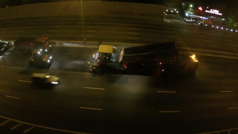 Flying over workers laying asphalt at night Footage