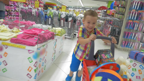 Happy boy in mall with a trolley full of party things Footage