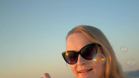 Young Woman in Sunglasses Blowing Soap Bubbles Footage