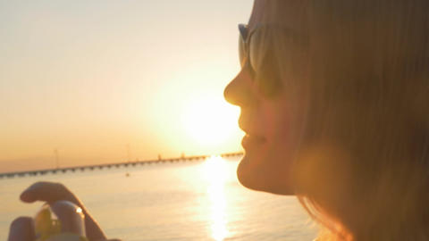 Woman Blowing Soap Bubbles at Sunset Footage