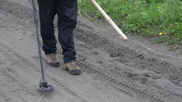 Treasure hunter walking on road, holding metal detector, scanning ground of road Footage