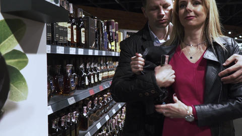A couple is stealing a bottle of alcohol from the supermarket Live Action