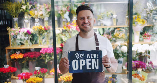 Attractive young man wearing apron holding open sign in flower store smiling Footage