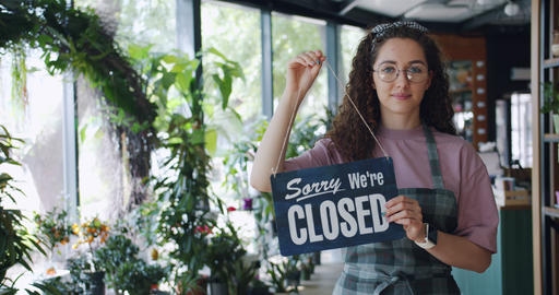 Portrait of attractive florist changing sorry we are closed sign to we are open Footage
