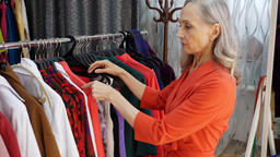Gray haired elderly woman choosing dress in fashionable clothing store. Elegant Footage