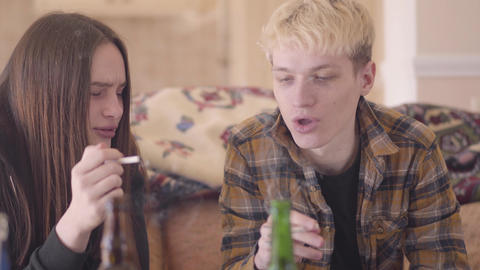 Portrait trouble teen friends sitting in front of empty alcohol bottles smoking Live Action