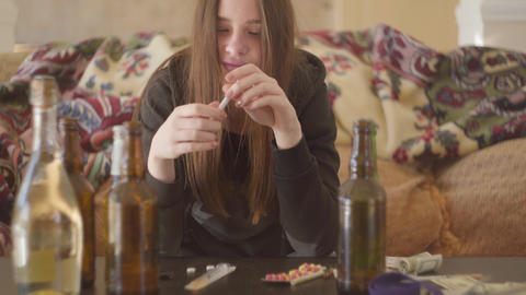 Portrait of a drug addicted girl who consumes alcohol and drugs. Addiction Live Action
