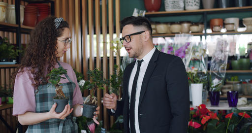 Cheerful people florist and customer discussing green plants in flower store Footage