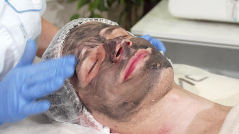Cosmetologist preparing face of male client for carbon facial peeling Live Action