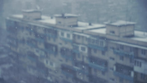Snow falls behind the window with blurred background of the neighborhood blocks Live Action