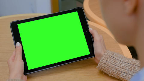 Woman looking at tablet computer with green screen in cafe Live Action