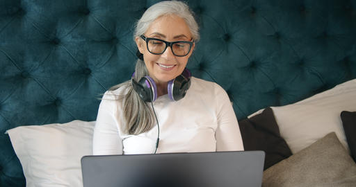Elderly Woman with Laptop in Bedroom Footage