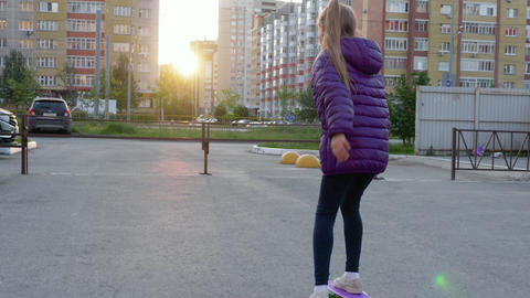 Girl teenager skateboarding on long board on city street while evening sunset Footage