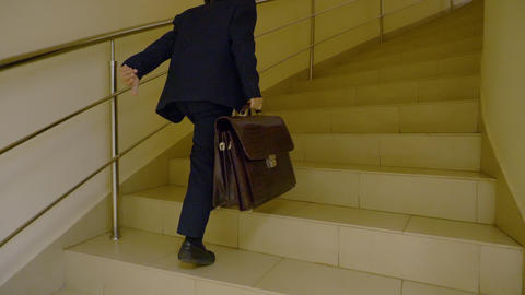 Young schoolboy with briefcase walking upstairs school hall. Young businessman Footage