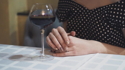 Indecision of people The hands of a young woman in evening dress with a glass of Footage