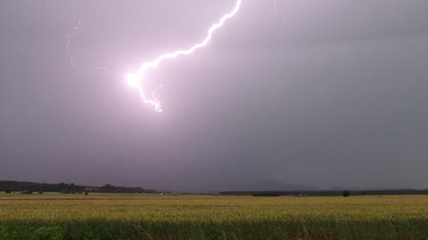 Real time thunderstorm with lightning bolts illuminating the sky above rural Footage