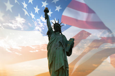 Double exposure with statue of liberty and United States flag blowing in the wind Fotografía