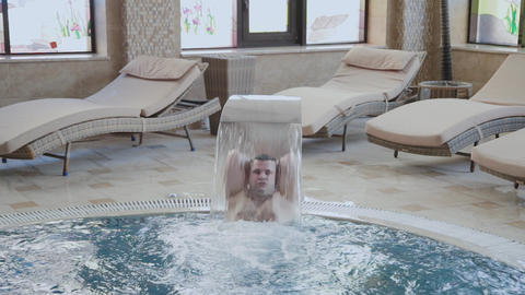 Cheerful man swims under a waterfall and poses in the pool Footage