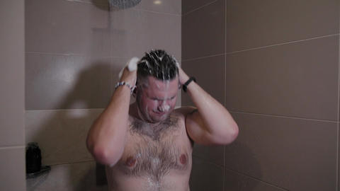 Cheerful funny man washes in the shower Footage