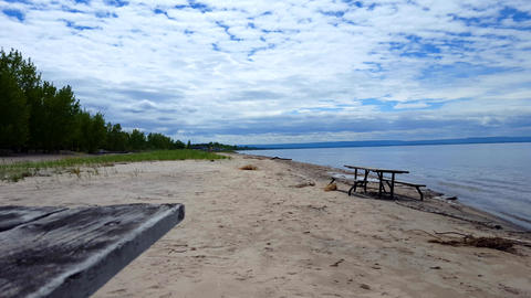 Picnic Table Along Beautiful Sand Beach Shore. Daytime Sunny Vacation Shoreline Beach Destination in Footage