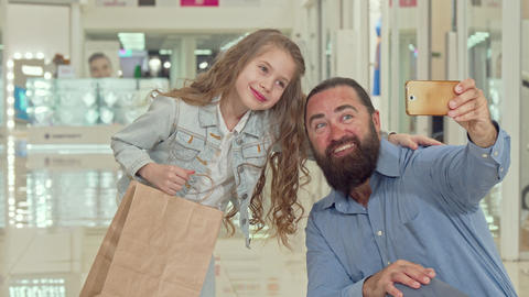 Adorable little girl taking selfies with her father at the shopping mall Footage