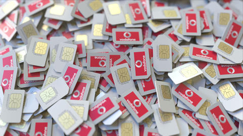 Pile of SIM cards with Vodafone plc logo, close-up. Editorial telecommunication ビデオ