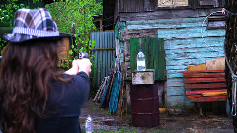 The girl in the hat shoots a gun and shoots a bottle of water Footage
