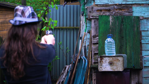 The girl in the hat shoots a gun, a bullet shoots a bottle of water Footage