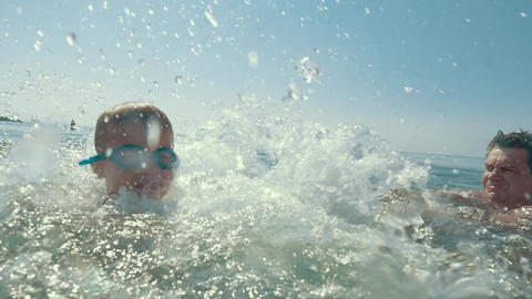 Boy Spinning Around and Splashing in the Sea Footage
