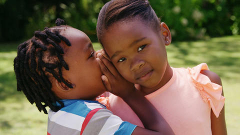 Little boy whispering a secret to his sister Footage