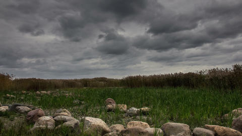 Gloomy dark clouds over the field and stones zoom-in Footage
