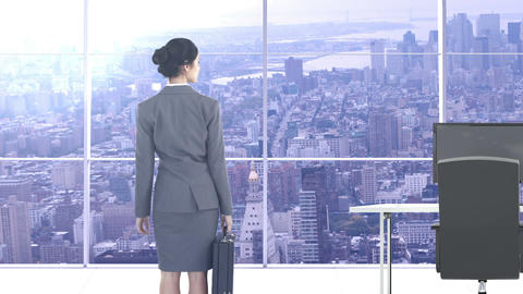 Rear view of businesswoman standing in office with briefcase Live Action