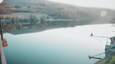 Beautiful artificial lake in the fall time, a man sitting on the jumper Footage