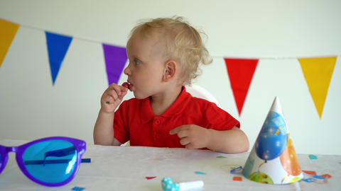 Little boy sucks a sweet candy on a stick. After birthday party. Gimbal shot GIF