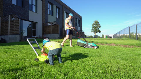 Man mowing lawn with lawn mower while son play with toy lawnmower. Gimbal GIF
