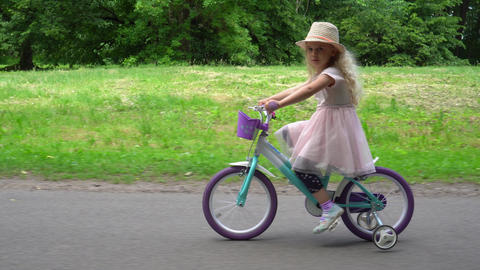 smiling cute girl cycling in the park. Gimbal parallel movement shot Live Action