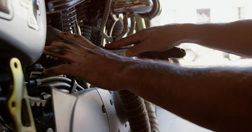 Male mechanic repairing motorbike in repair garage 4k Live Action