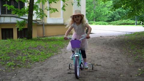 Pretty little female model in pink dress ride bike on four wheels. Gimbal shot GIF