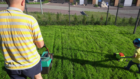 Son pushing a toy lawn mower while dad mows with his. Gimbal shot GIF
