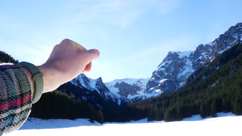 Hand stretches to the sun and mountains. The concept of the sun's glow from the Live Action