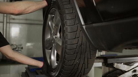 Mechanic checks suspension at the car service station, suspension repair Live Action