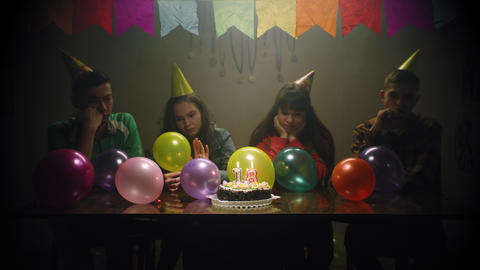 sad teenagers sit at table with cake for eighteenth birthday Live Action